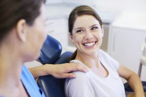 A pretty young woman having a conversation with her friendly dentist
